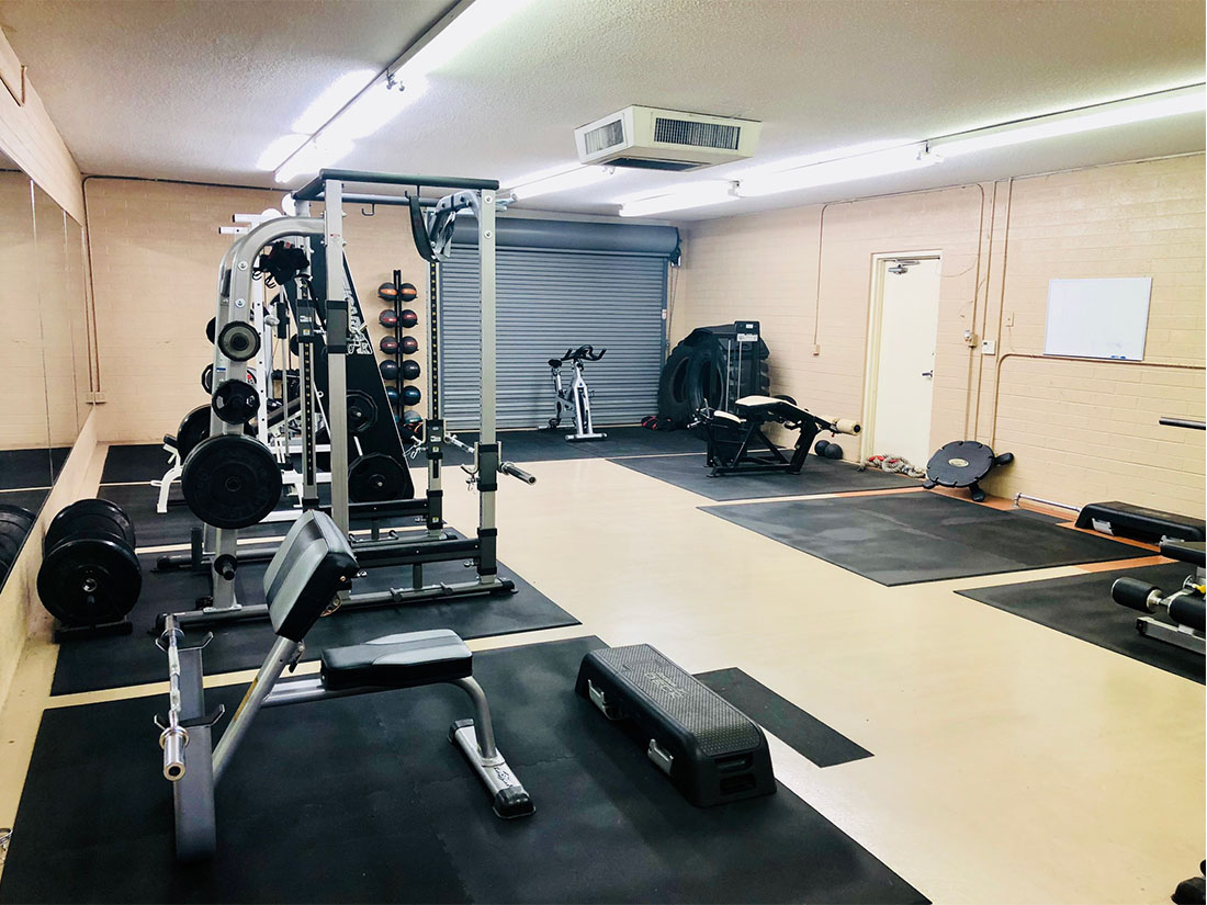 photo 6 of the back room of FIIT by Jason Smith facility showing rebok deck, bicep curl machine, leg curl machine, medicine ball rack with medicine balls, squat rack and weight plates for resistance training, cardiovascular training and functional training in Phoenix, AZ
