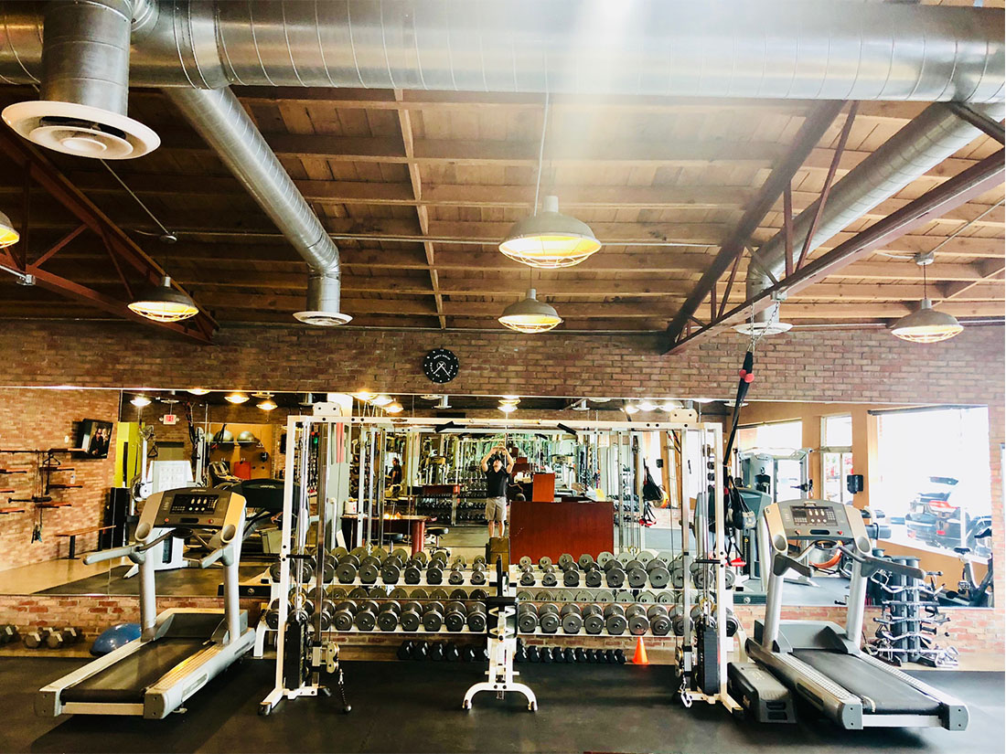 photo 4 of FIIT by Jason Smith facility showing treadmills, dumbbell racks with dumbbells, cable crossover machine, and attachments tree