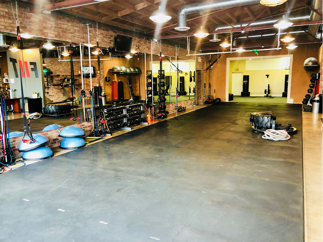 photo of FIIT by Jason Smith facility showing open space with bosu balls, dumbbell racks, TRX bands, battle ropes, agility ladder, resistance bands, tire flip and more to maximize weight loss and muscle gain