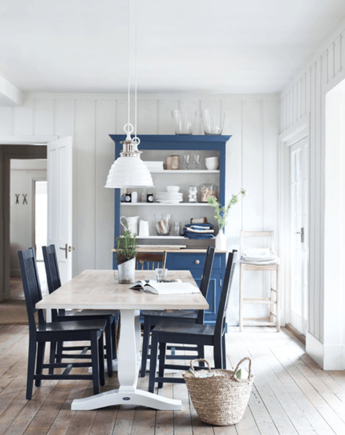 white cottage style dining room with marine blue hutch