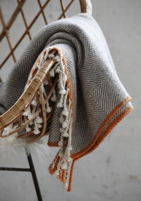gray plaid throw blanket with burnt orange edge