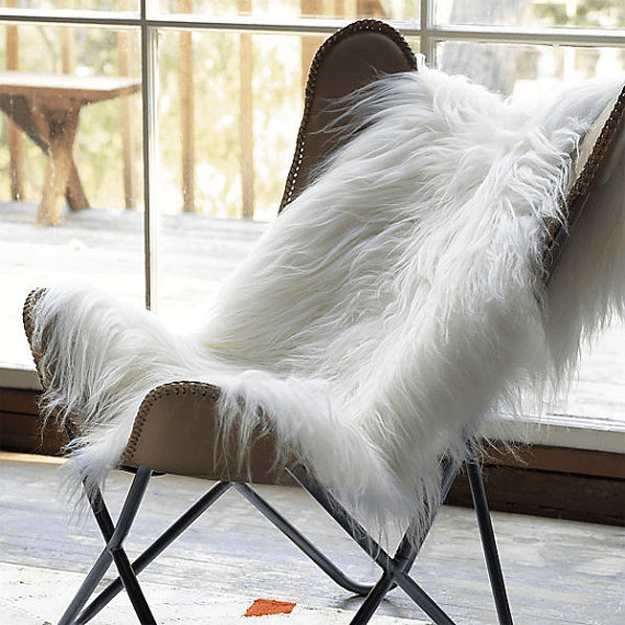 ivory white sheepskin rug draped over leather sling chair