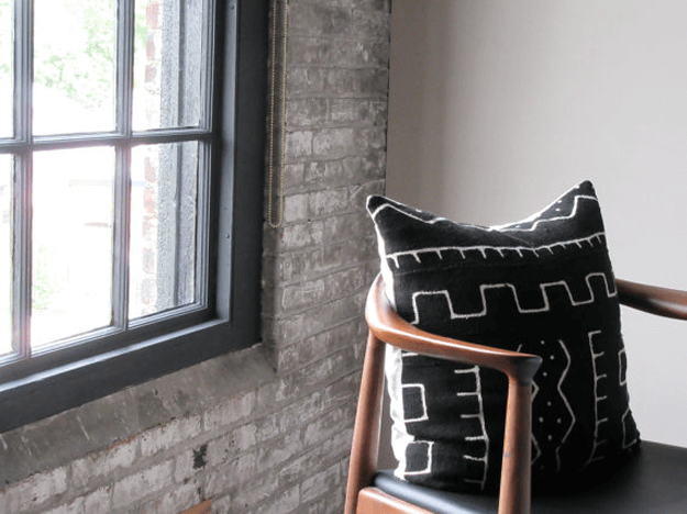 black mudcloth tribal pillow on mid-century mod chair