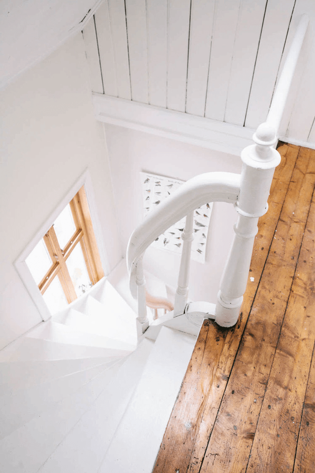 white stairwell with camel brown wood accents