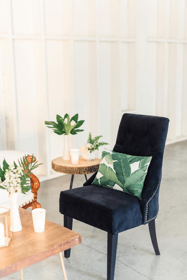 banana leaf pillow on dark navy velvet chair