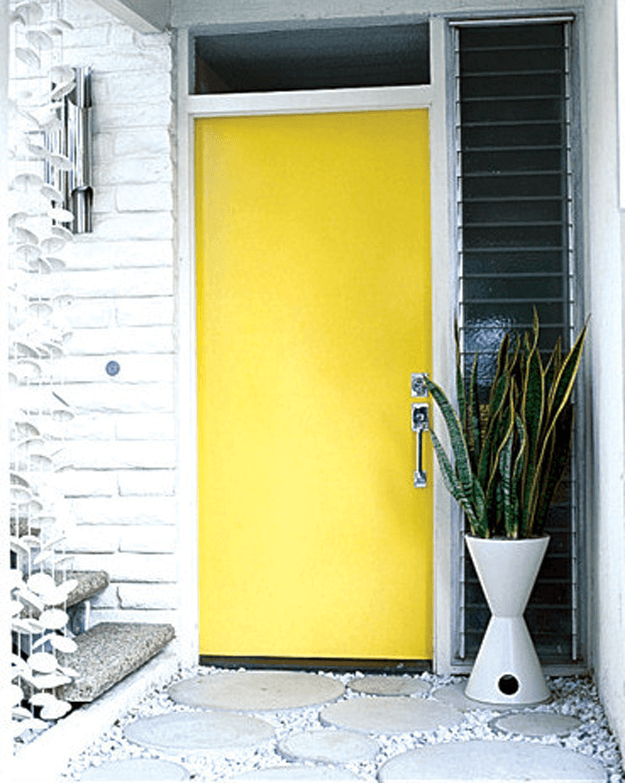 bright yellow front door in white painted brick wall