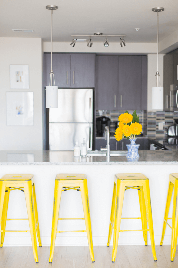 modern kitchen with bright yellow stools