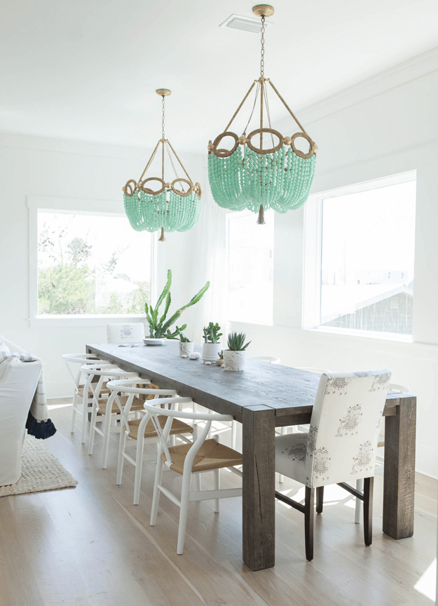 white dining room with mint green chandeliers