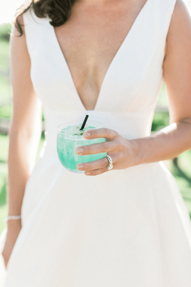 woman in white dress holding mint green drink