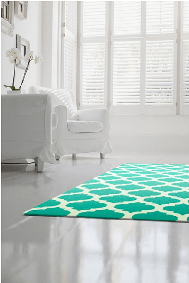 white living room with jade green patterned rug