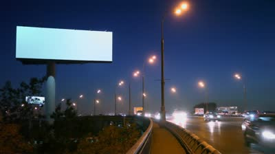 stock-footage-cars-rid-by-highway-with-empty-advertising-billboard-on-sidelines-at-night