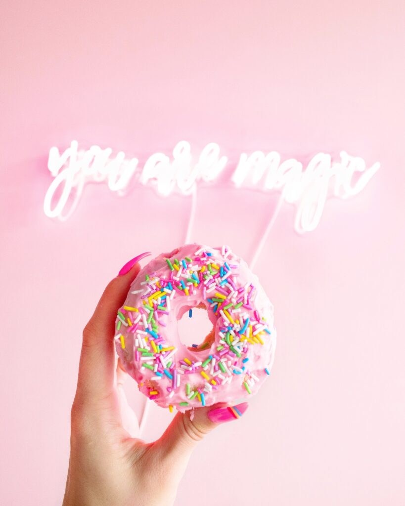 woman-holding-donut-with-sprinkles-2801980