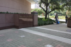 FloodBreak pedestrian floodgate has matching granite sidewalls and is covered with pavers