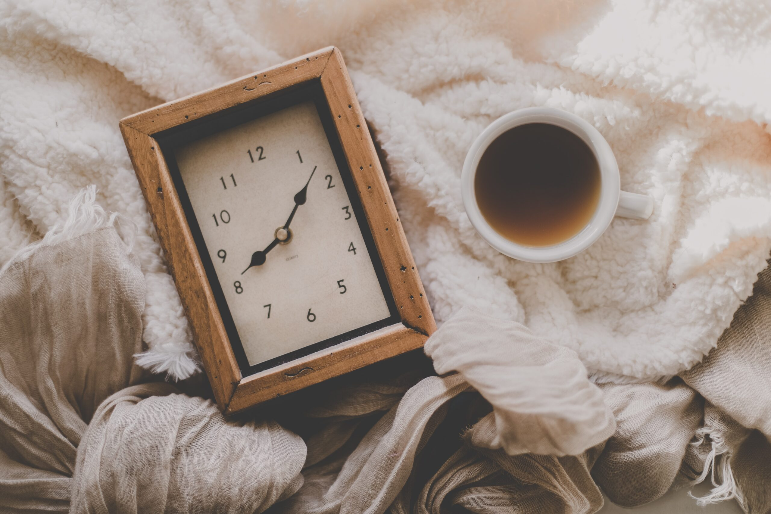 time and coffee on a bed