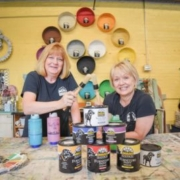 Laura and Swooz sit with Black Dog Salvage furniture paint in Black Dog Salvage's retail showroom