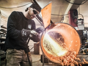 a man welding a cylndrical piece of metal