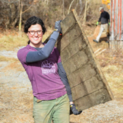 Grayson Goldsmith carries a piece of salvaged wood at the Taylor family farm