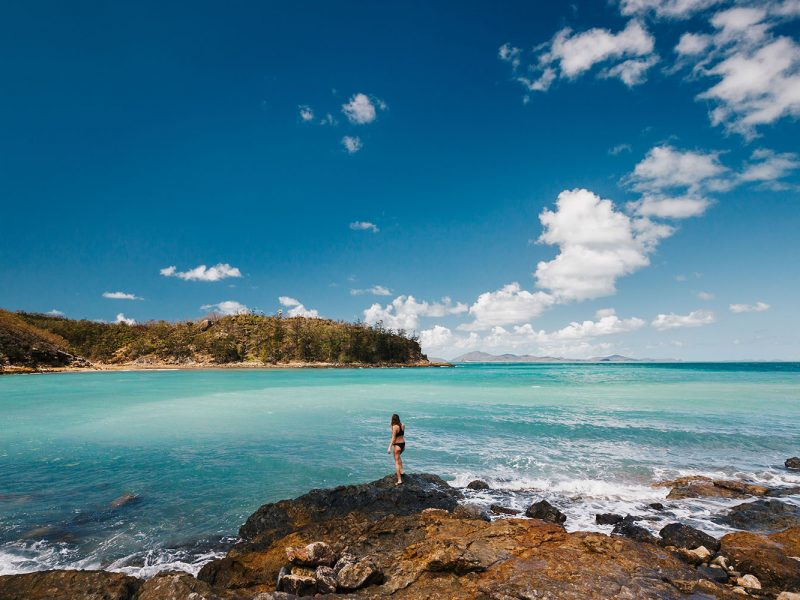 Girl standing on the edge of the Beach at Hamilton Island in the Whitsundays
