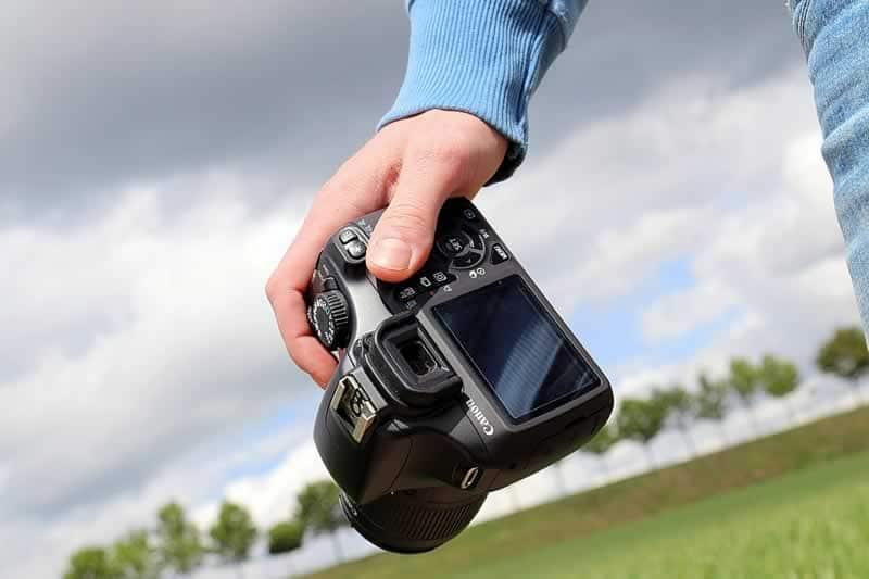 mão segurando máquina câmera fotográfica canon