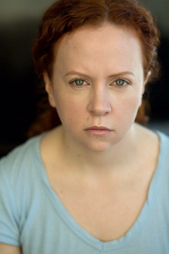 Stephanie Hamer gives a serious look for headshot in light blue shirt