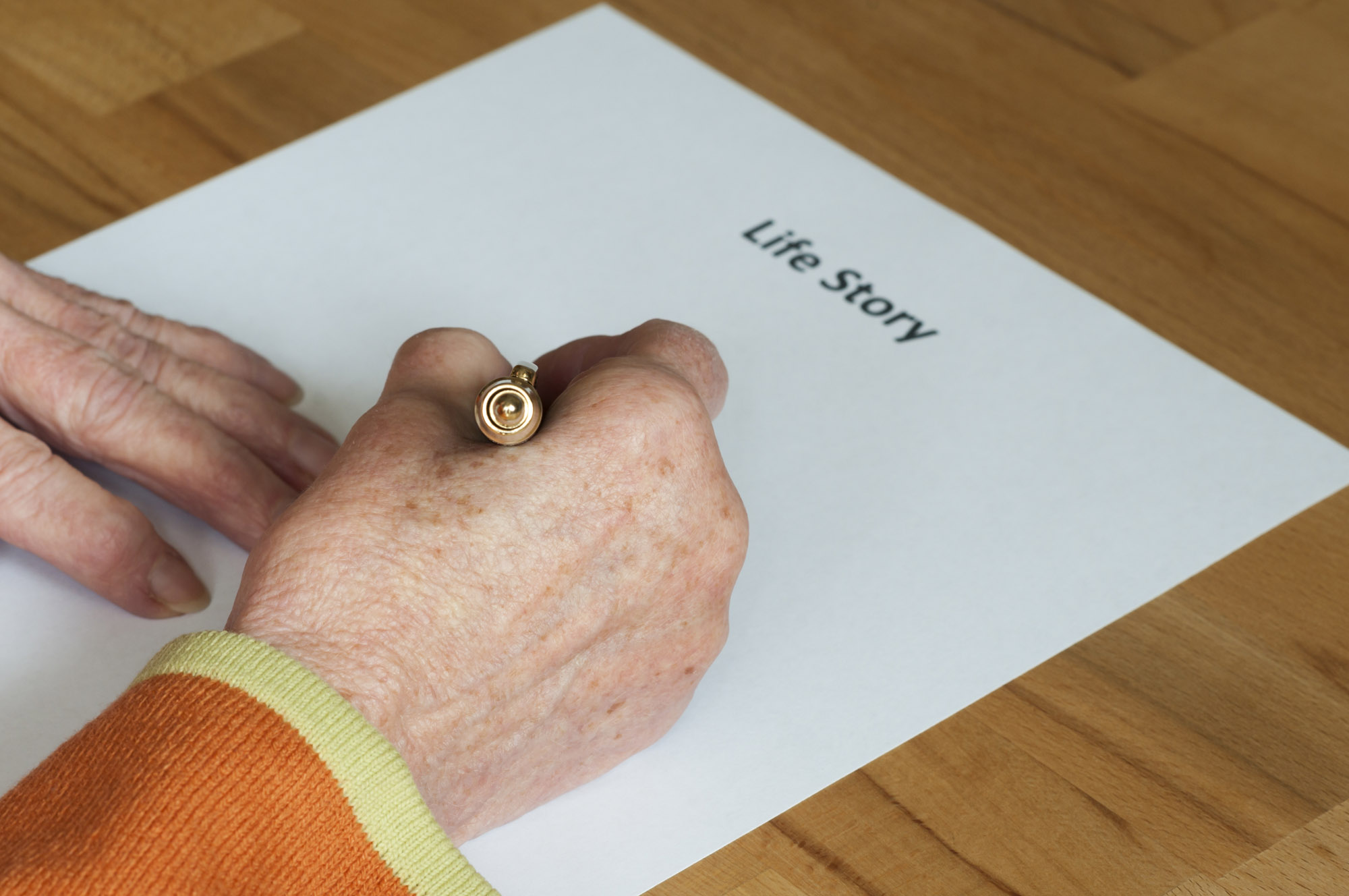 Senior writes her memoirs on a white sheet of paper with heading.