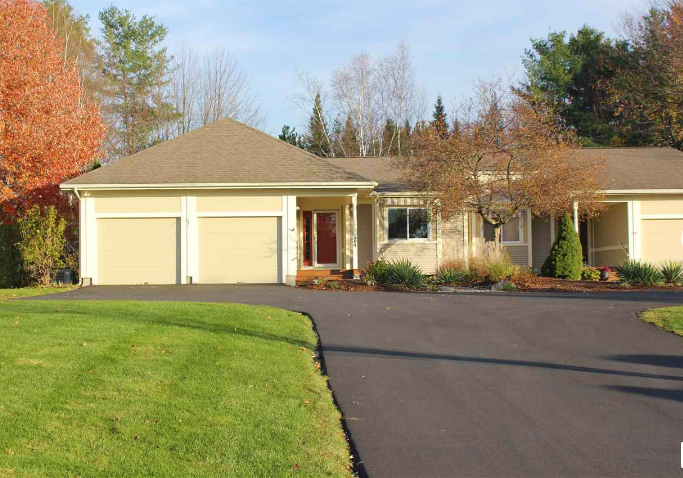photo of a home single level living and two garages, green lawn and paved driveway in vermont
