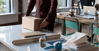 Person packing a cardboard box, brown shirt with torso visible and hands on the box, packing materials around