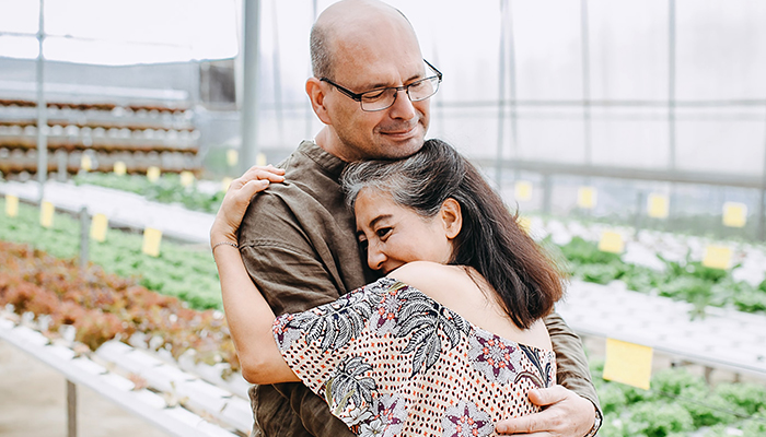 Woman, a mother hugging her adult son in a greenhouse