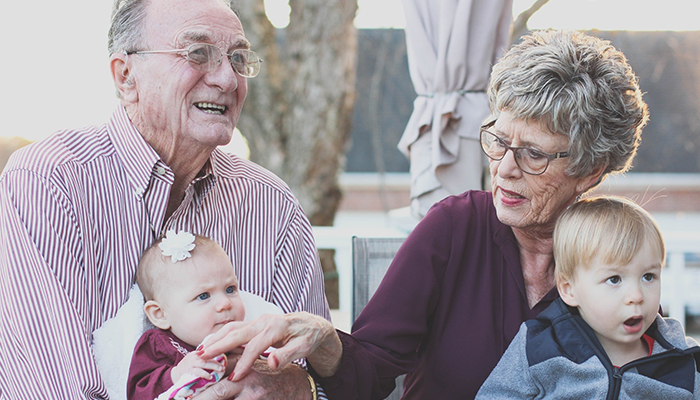 Elderly man and woman sitting with a baby and toddler grandchildren in their laps