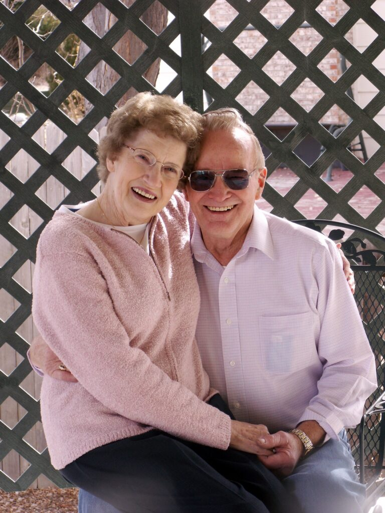Older couple, woman in a pink blouse sitting in man's lap, man in lavender button down