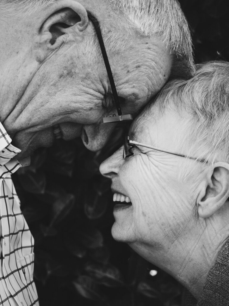 Older couple with forehead to forehead and smiling at each other