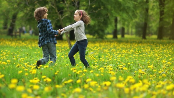 Two choldren grasping hands spinning in the field
