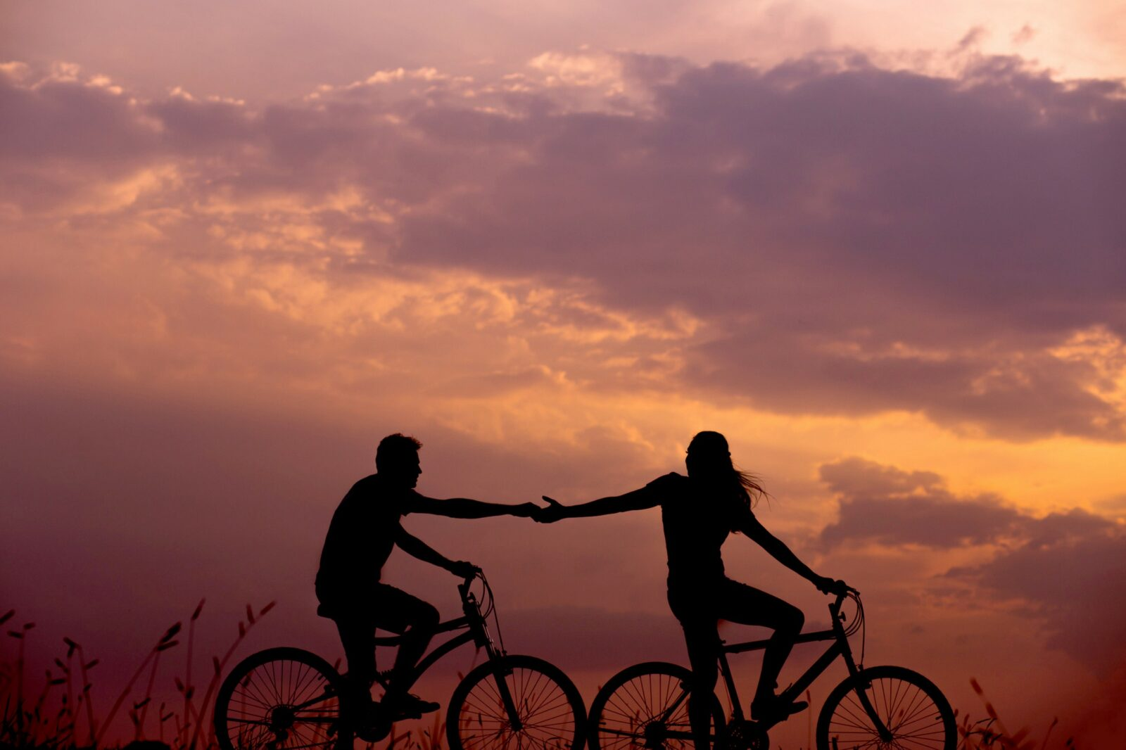 Sunset, two bike riders silhouetted in the foreground. The lead lady is reching back and grasping hands with the male. Romantic.