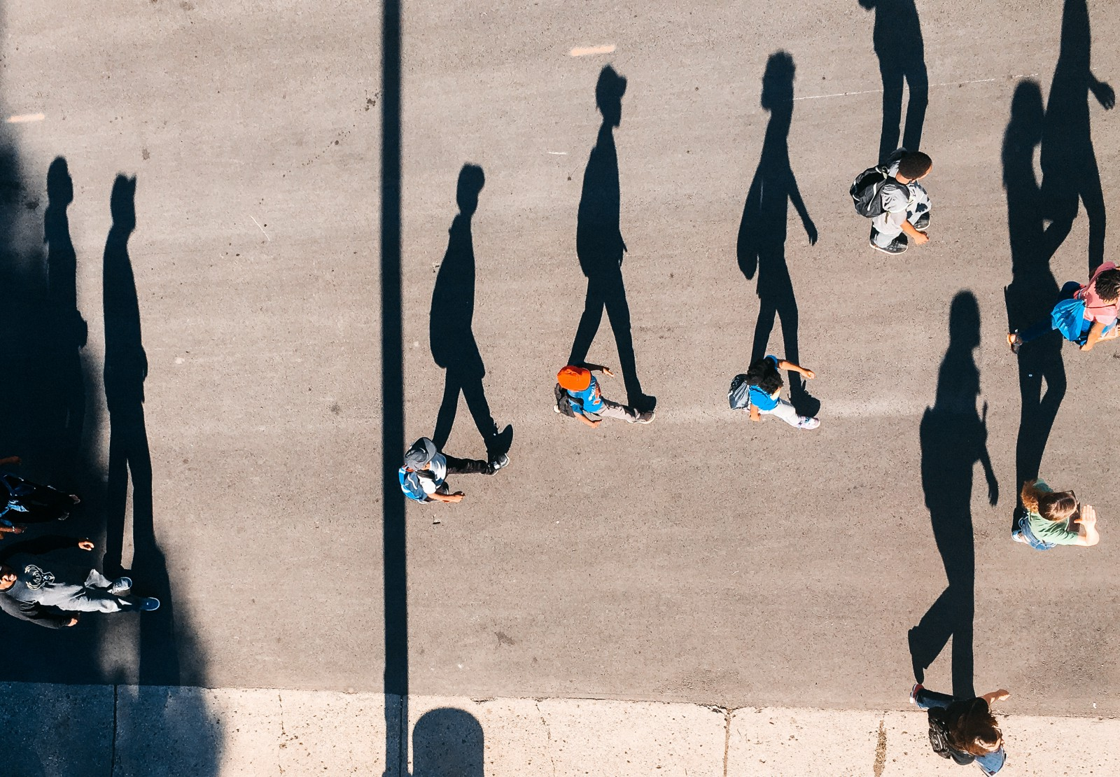 Top dpwn view of a line of people walkinf left to right on the picture. The sun is low in the sky causing their shadows to spread out beside them. Making it look like the shadows are walking down the road in a two dimensional image.