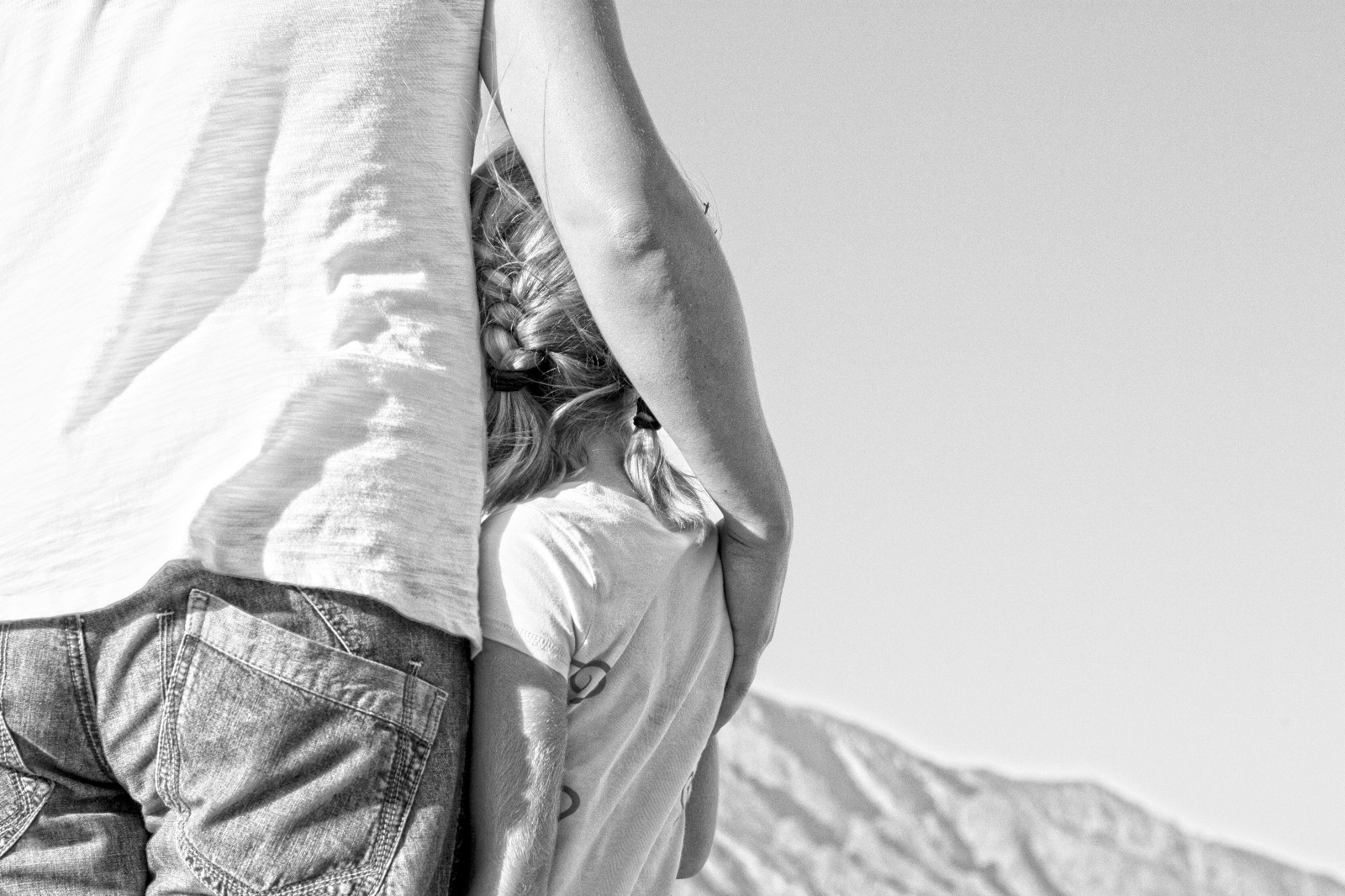 Father and daughter looking off into the distance in a half hug embrace. Black and White photo.