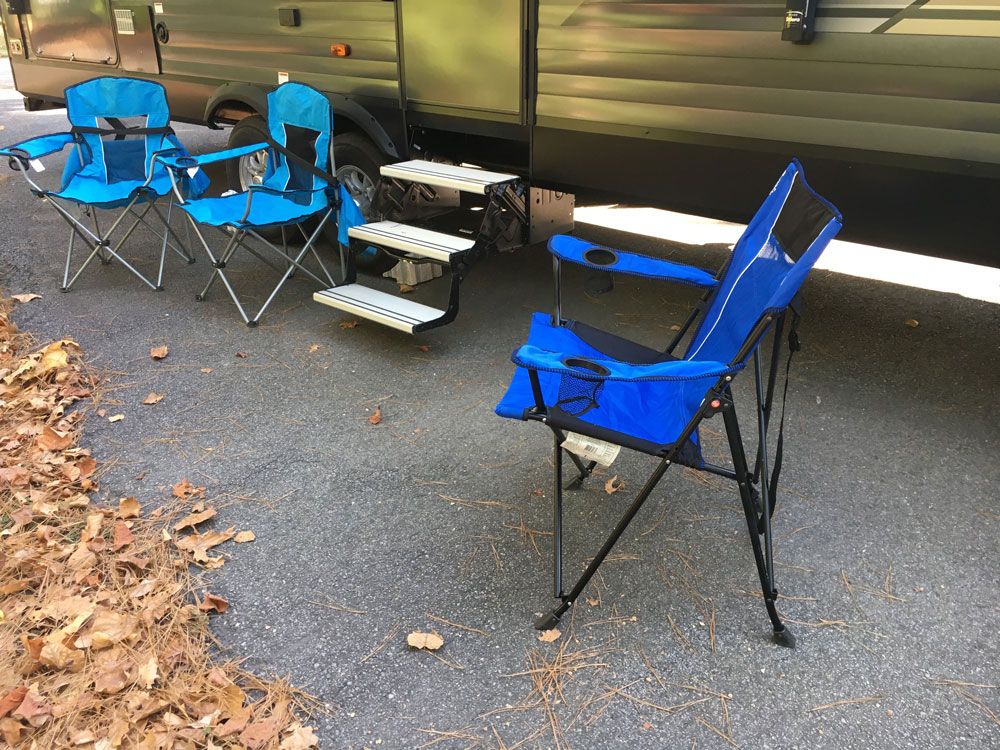 kijaro camping chair and regular bag chairs next to travel trailer