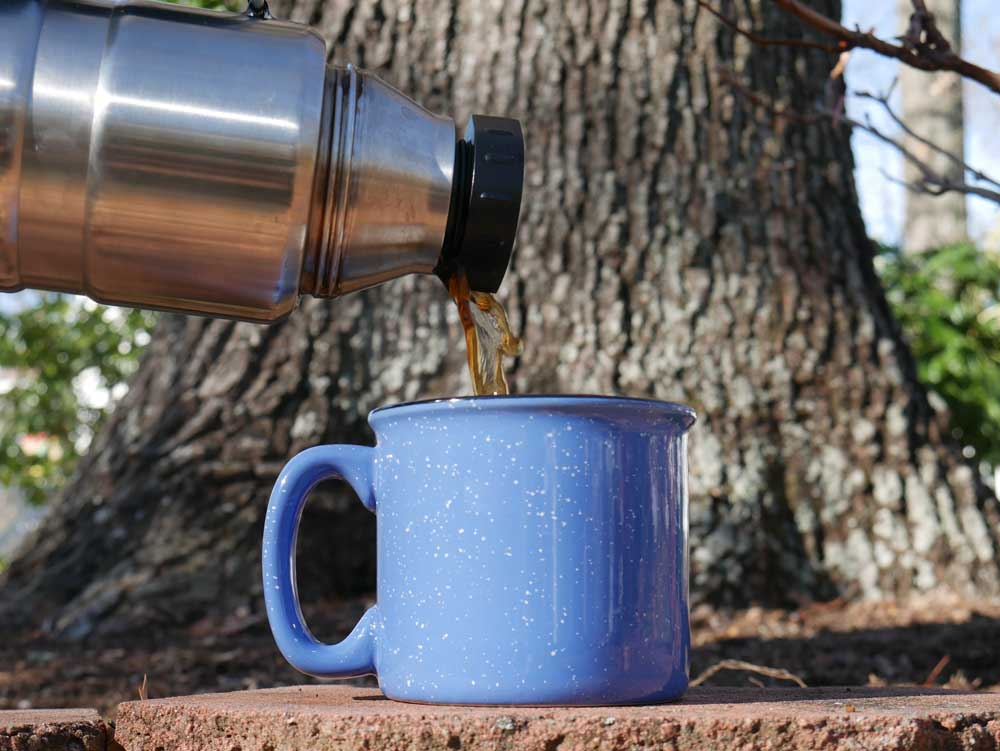 Pouring Coffee From Thermos Into Mug for Camping Coffee