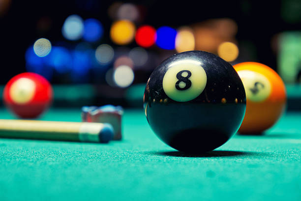 Close-up picture of an Eight Ball with a cue stick, chalk cube and Five Ball in the background