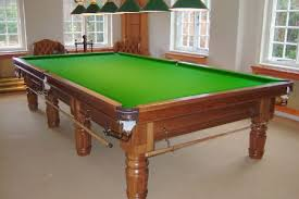 A pool table that was just refelted with new green felt by North Coast Pool Tables