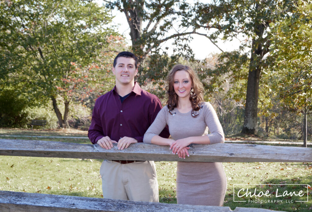 Autumn Engagement Photos leaning on fence post at Hartwood Acres mansion in Pittsburgh, PA