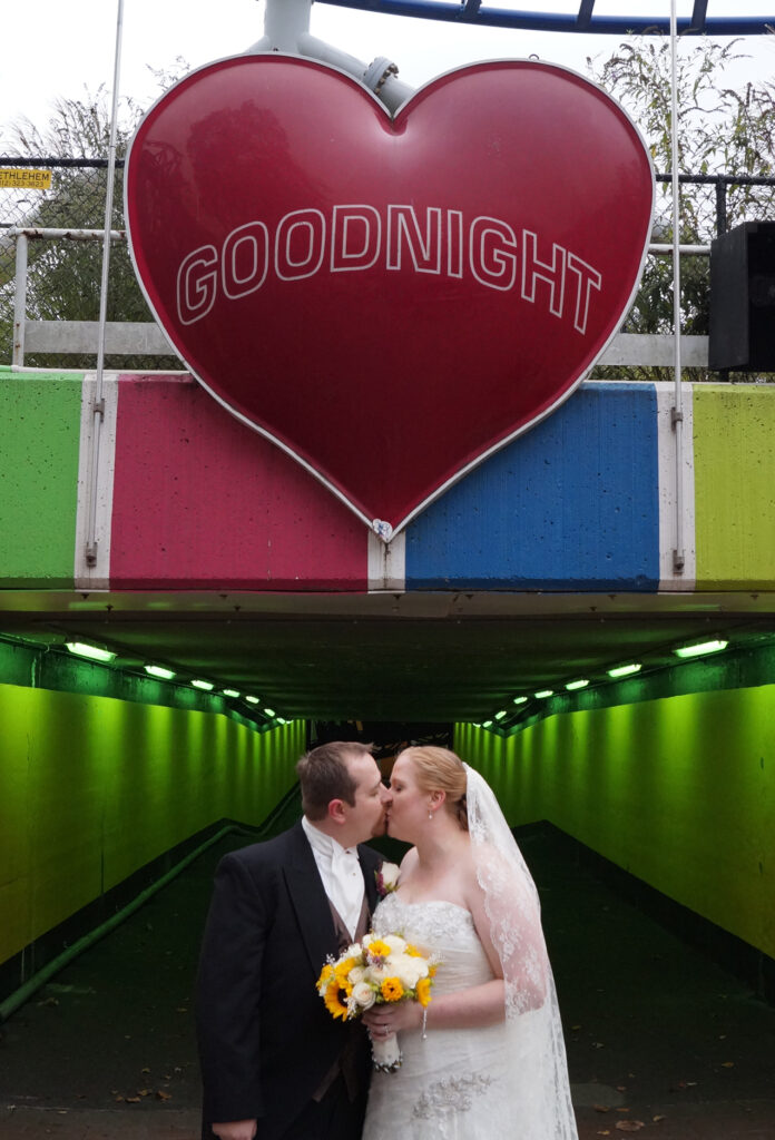 Bride and groom kissing under the the goodnight heart sign at Kennywood Park in Pittsburgh, PA