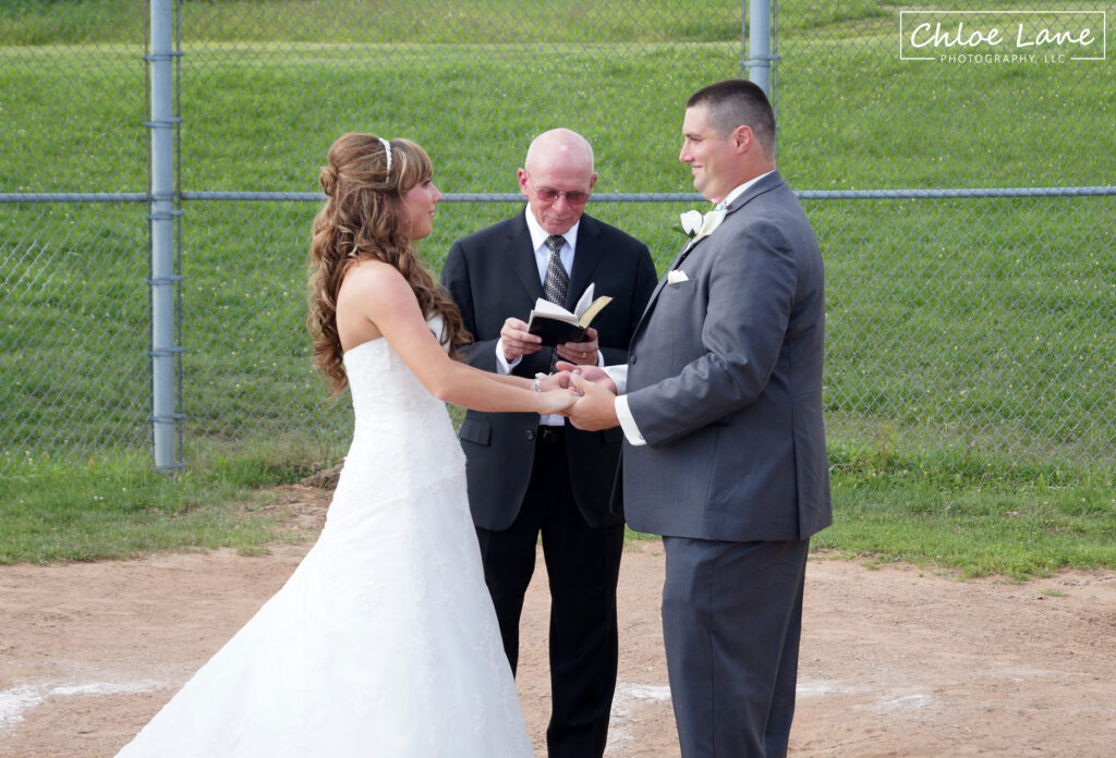 Softball wedding theme, bride and groom getting married at home plate in Scottdale Pennsylvania