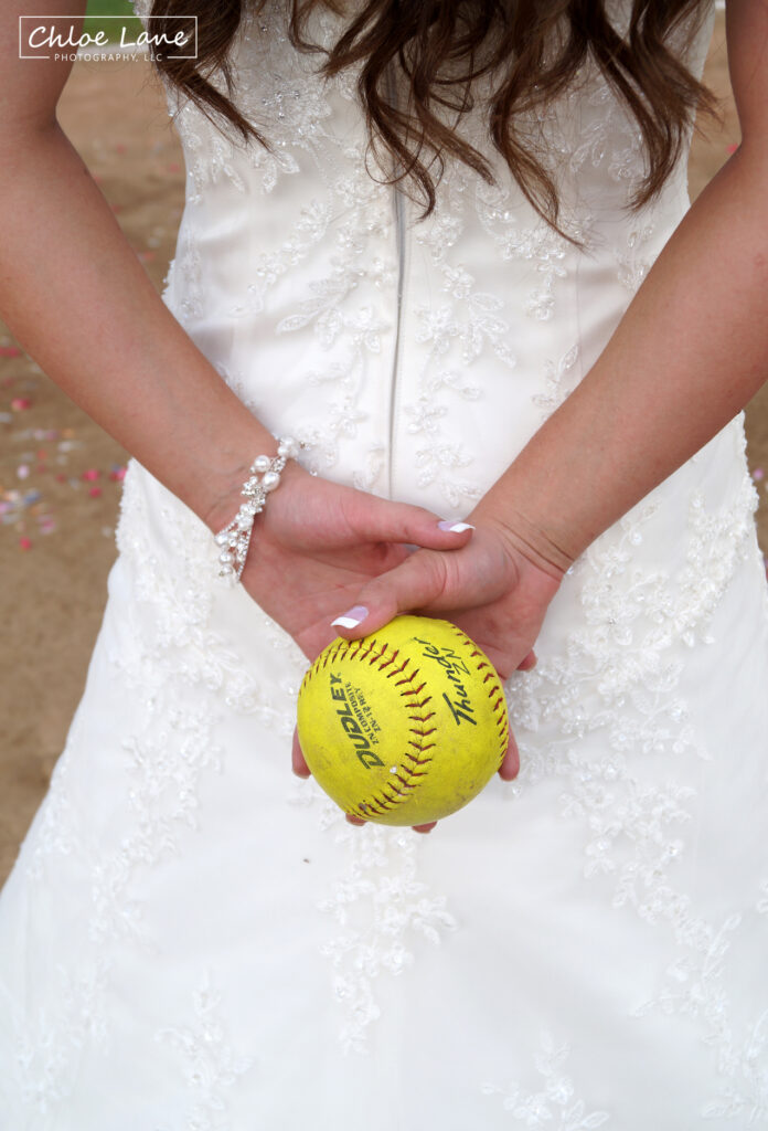 Softball wedding theme, bride pitching softball to her new husband in Scottdale Pennsylvania