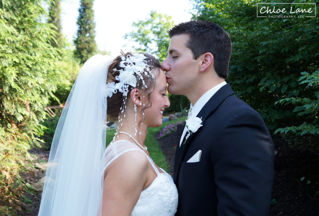 Bride and Groom kissing in garden courtyard