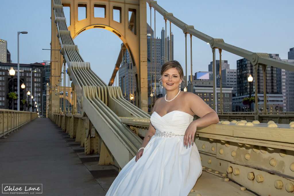 Bride sitting on Clemente Bridge with City of Pittsburgh as the background wedding photo