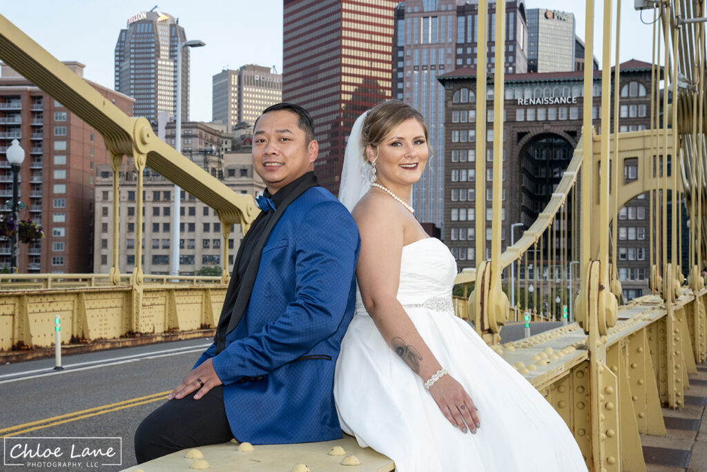 Bride and groom sitting on Clemente Bridge with Downtown Pittsburgh in the background