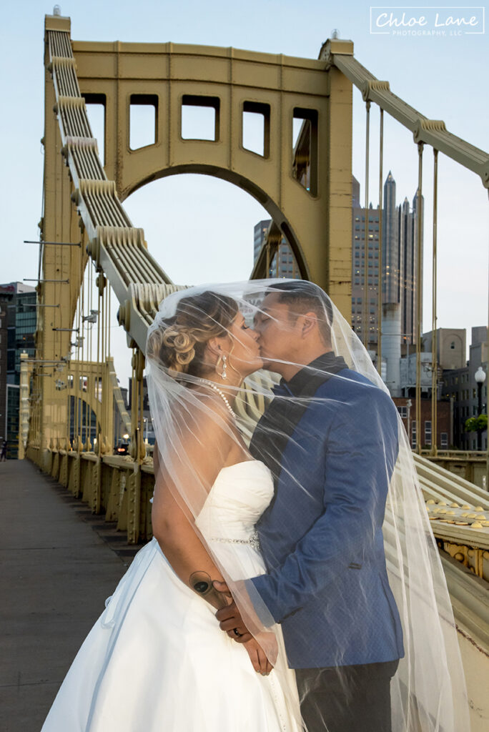 Bride and groom kissing on Clemente Bridge with City of Pittsburgh as the background wedding photo