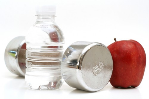 shot of a bottled water with fitness weight & apple