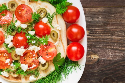 Pita with hummus, cheese, cherry tomatoes, olives and greenery