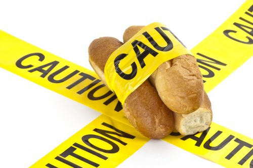 Dietary concept or gluten/wheat allergy warning (Slices of fresh French bread wrapped in yellow caution tape)